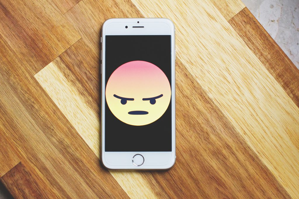 A phone displaying an anger emoji