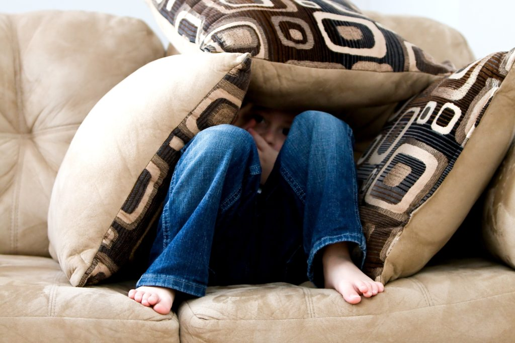 A child hiding under couch cushions