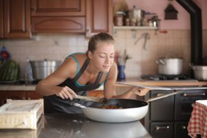 A woman leaning over a pan, smelling the food as it cooks